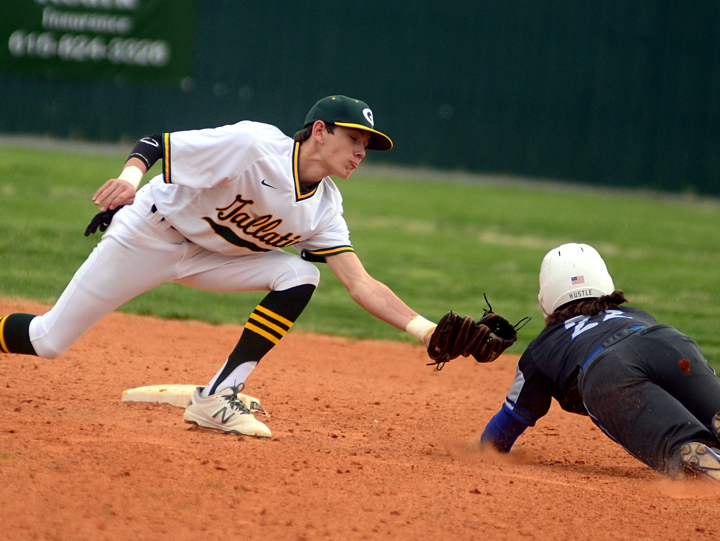Gallatin High freshman shortstop Brady Harris attempts to tag Lebanon sophomore Jonathan Presley during fourth-inning action.