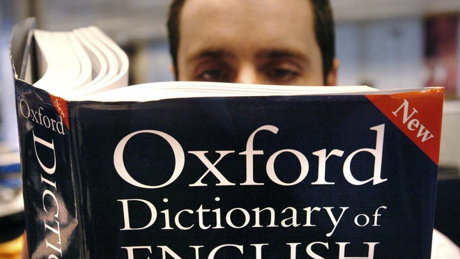 A man reads a copy of the Oxford Dictionary of English.