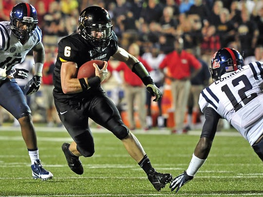 Vanderbilt quarterback Austyn Carta-Samuels (6) runs for a first down against Ole Miss defensive back Tony Conner during the second quarter at Vanderbilt Stadium in Nashville, Tenn., Thursday, Aug. 29, 2013.