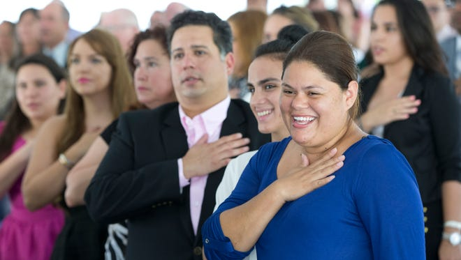 Jennifer Ariadna Martinez, front right, of Nicaragua and other new citizens recite the Pledge of Allegiance during a U.S. Citizenship and Immigration Services naturalization ceremony on the campus of Florida International University on July 6, 2015, in Miami.
