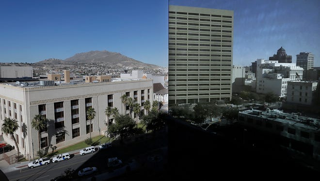 The old U.S. Courthouse in Downtown El Paso is reflected on the side of the El Paso County Courthouse, left. President Barack Obama signed a bill into law to name the building after former El Paso Mayor and U.S. Rep. R.E. Thomason.