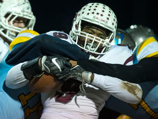 Henderson County's Dada Simpson (9) gets tackled as
