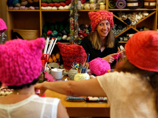 "Jayna Zweiman, background, co-creator of the ""pussyhat,"" wears one that she knitted while knitting another one on Jan. 6, 2017 at The Little Knittery in Atwater Village, Calif."