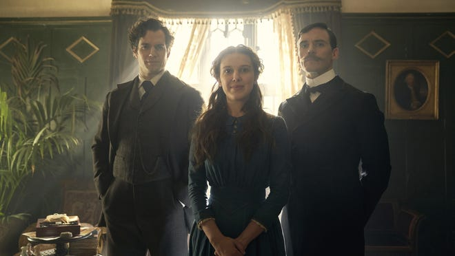 """From left, Henry Cavill playikng Sherlock Holmes, Millie Bobby Brown and Enola Holmes and Sam Claflin at sibling Mycroft Holmes in a scene from """"Enola Holmes."""""""