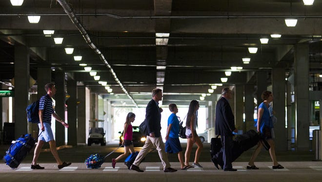 In this file photo, travelers make their way to the car rental lot at Southwest Florida International Airport.