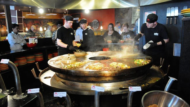 HuHot Mongolian Grill employees stir fry food orders at the restaurant's Green Bay branch in this 2010 file photo.