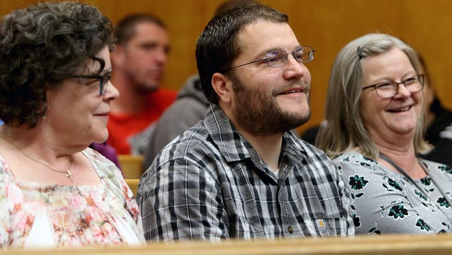 Nathan Hempel, center, smiles as Kitsap County District Court judge Claire Bradley talks about his accomplishments in the county's Behavioral Health Court diversion program. He was at the commencement ceremony with his mom, Irene Montgomery, left, and his care coordinator, Carol Varney, right, from the Kitsap Mental Heath Services.
