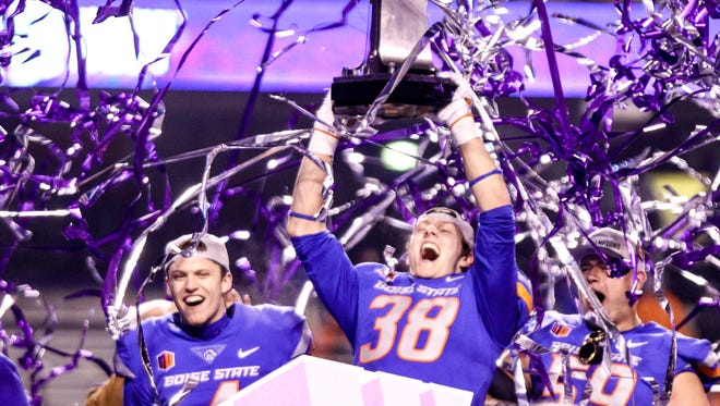 Boise State linebacker Leighton Vander Esch and his teammates celebrate with the trophy after winning the 2017 Mountain West championship game.
