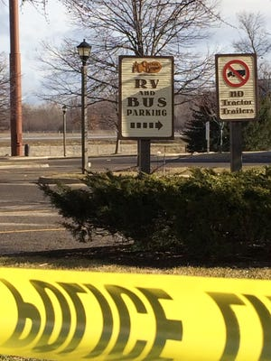 Police tape surrounds the area of a random shooting  in the parking lot of a Cracker Barrel restaurant Sunday in Kalamazoo, Mich., where three were killed and a fourth person wounded.