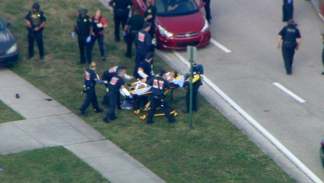 In this frame grab from video provided by WPLG-TV, emergency personnel wheel an injured person from the Marjory Stoneman Douglas High School in Parkland, Fla., following a shooting there on Wednesday, Feb. 14, 2018.