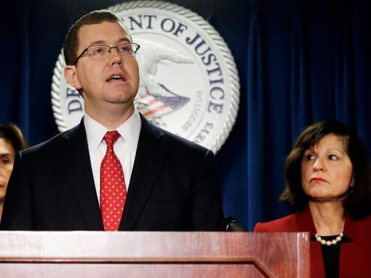 Associate Attorney General Stuart Delery speaks after U.S. Attorney Carmen Ortiz, right, announced indictments of 14 owners and employees from the New England Compounding Center Wednesday in Boston.