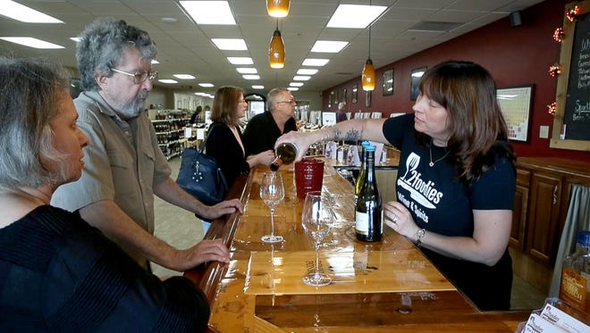 Greece residents Linda and Oliver Willy taste some wine poured by 2Foodies Wine & Spirits owner Carrie Morabito before a wine tasting event.