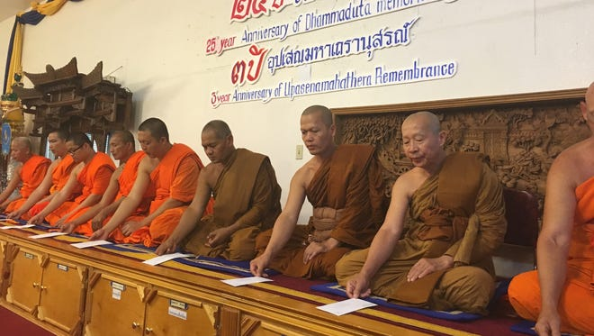Monks at the Wat Prokunaram Buddist temple pray during a ceremony to honor nine murdered in 1991.