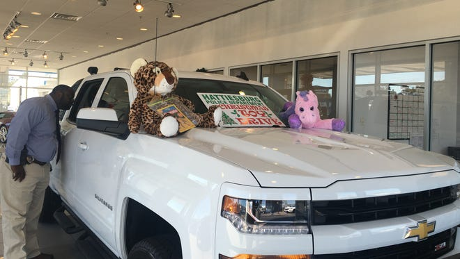 Hattiesburg police Sgt. Vincent Brown looks inside a truck that will be used for a Christmas toy drive at Ryan Chevrolet. Toy donations will be accepted through Dec. 12.