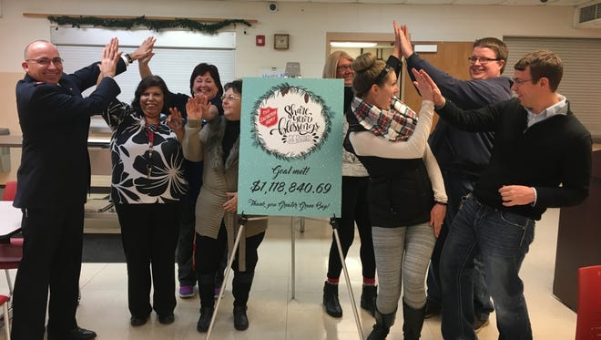 Organizers of The Salvation Army of Greater Green Bay celebrate after announcing the charity organization raised more than $1.1 million during its Christmas campaign.