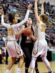 Delone Catholic's Bradi Zumbrum eyes the basket against York Catholic's Jania Wright and Katy Rader in the second half of the PIAA District 3 Class 3A girls' basketball title game Thursday, March 2, 2017, at the Giant Center in Hershey. York Catholic defeated Delone Catholic 57-46 to earn its 11th district championship in 12 years, as well as head coach Kevin Bankos' 300th career win.
