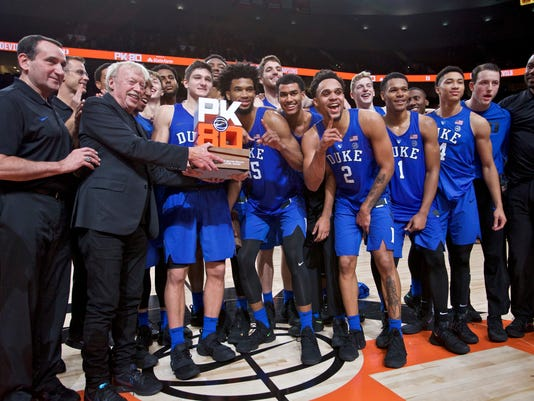 Nike founder Phil Knight presents the championship trophy to Duke head coach Mike Krzyzewski, left, after an NCAA college basketball game against Florida in the Phil Knight Invitational tournament in Portland, Ore., Sunday, Nov. 26, 2017. Duke won 87-84. (AP Photo/Craig Mitchelldyer)