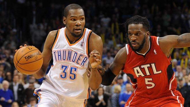 Oklahoma City Thunder small forward Kevin Durant drives to the basket against Atlanta Hawks small forward DeMarre Carroll at Chesapeake Energy Arena.
