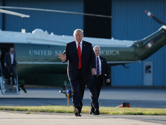 President Donald Trump waves as he walks from Marine