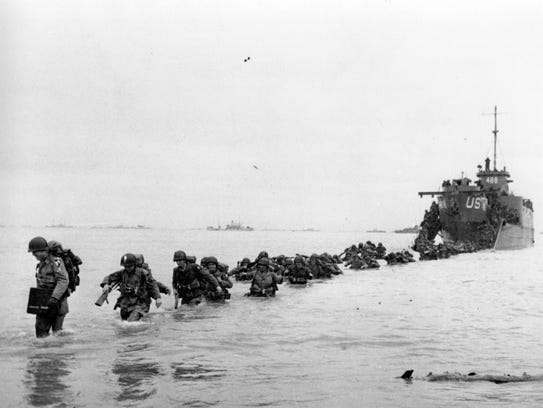 Men trudge through the water to shore during the D-Day