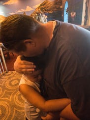 Cohen Powell is hugged by his father Robbie Powell.
