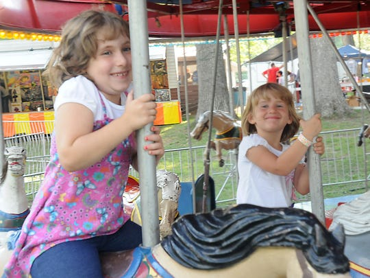 Olivia Gelwicks and Destini Carrol, of Path Valley ride the merry-go-round at the 2012 Path Valley Picnic.