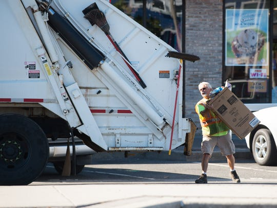 Butch Clay, a trash man for Rehoboth Beach, puts a cardboard box into the trash truck on Rehoboth Avenue.