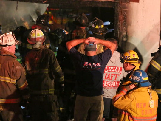 Firefighters work to free a trapped collegue at the