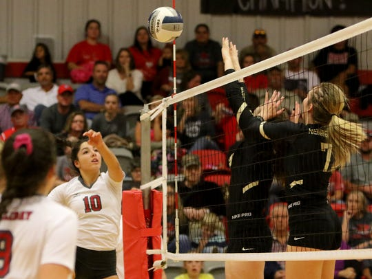 Holliday's Bree Zellers hits the ball away from Henrietta