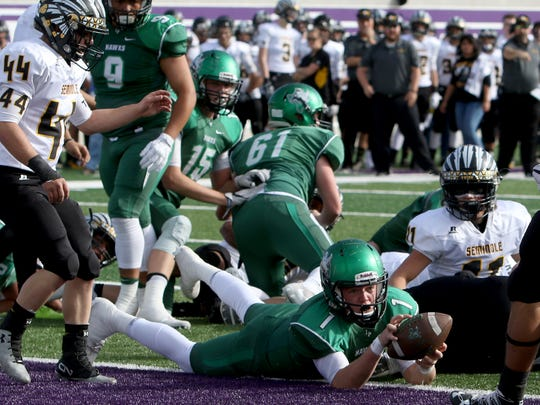 Iowa Park's Trent Green rolls over a Seminole defender