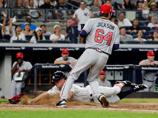 New York Yankees' Brett Gardner, left, slides past Atlanta Braves relief pitcher Luke Jackson to score on a wild pitch by Jackson during the fourth inning of a baseball game Tuesday, July 3, 2018, in New York.