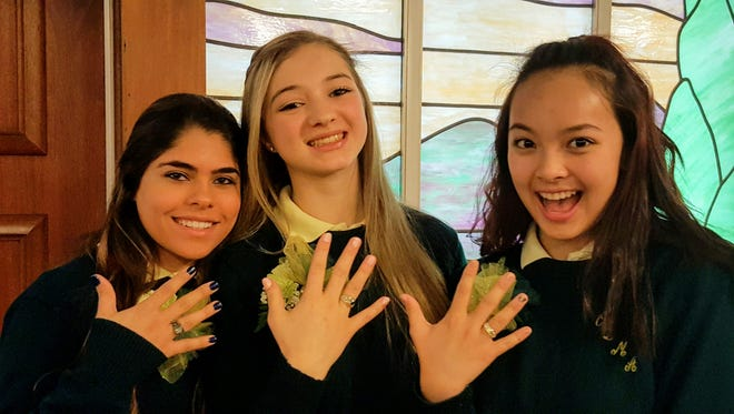 (From left) Gianni Richwine, Allyson Daley and Juliehan Nguyen, juniors at Our Lady of Mercy Academy, show off their new class rings.
