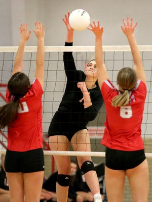 Moundridge's Kate Eichelberger (11) spikes the ball past Trinity Catholic's Abby Zipprich (10) and Becca Hammersmith (6) Thursday evening. Moundridge defeated Trinity Catholic in two matches 25-23, 25-14 and  26-24, 25-23.