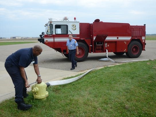 Battle Creek Firefighter Ed Marshall and Lt. Richard Teinert fill a crash truck with water at the Battle Creek Air National Guard Fire Station in 2014.
