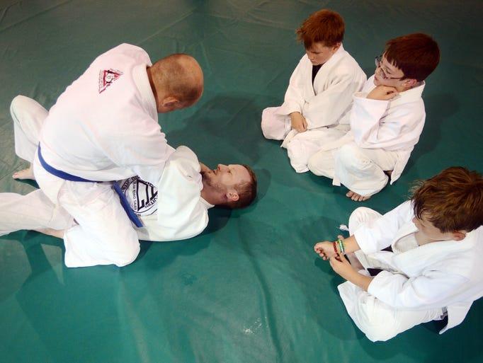 Jiu-Jitsu instructors Chris Joy, top, and Keith Strickland, bottom, demonstrate how to pull out of a choke hold Tuesday during martial arts class at Gracie Jiu-Jitsu.