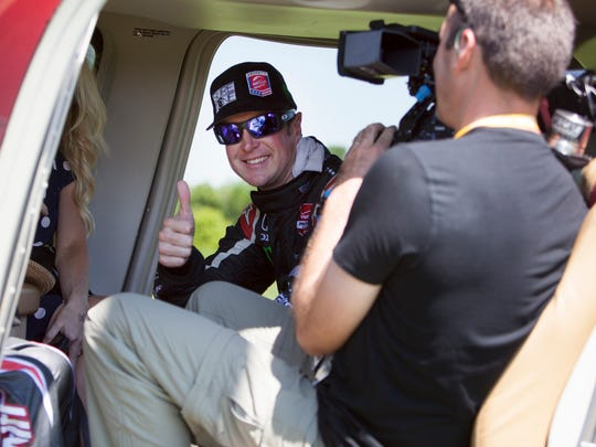 Kurt Busch gives a thumbs up after climbing into an awaiting helicopter at  the end of the Indianapolis 500 Sunday, May 25, 2014 at the Indianapolis Motor Speedway.  He is flying to race in the Coca Cola 600 at Charlotte Motor Speedway.