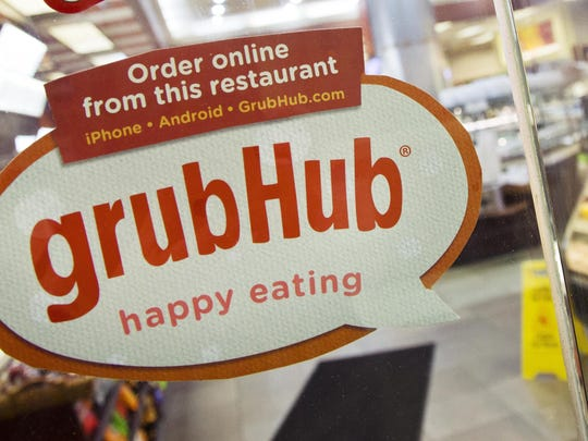 A sign for GrubHub is displayed on the door to a New York restaurant. The owner of KFC and Taco Bell, is teaming up with Grubhub to expand its delivery business.