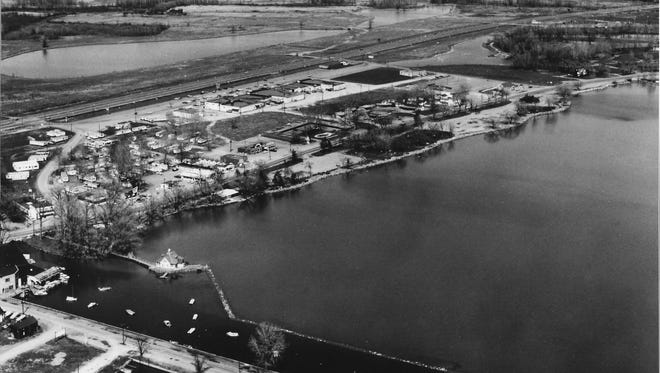 Canandaigua Lake's north shore is pictured in this aerial photograph taken prior to 1969. The swimming school and its access platform from the shore, a gift from Mary Clark Thompson, are visible, along with Eastern Boulevard and the newly constructed Parkway Plaza.