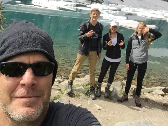 """Iowa wrestling coach Tom Brands unofficially calls himself the """"selfie king."""" Here, he snaps a beauty at Glacier National Park in Montana in July 2016. The children, from left: Tommy, 17; Madigan, 19; and Kinsee, 18."""
