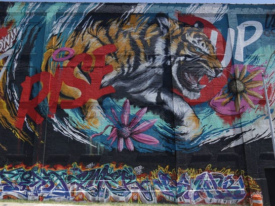 """Rise Up,"" a mural by Meggs, on Russell Street."
