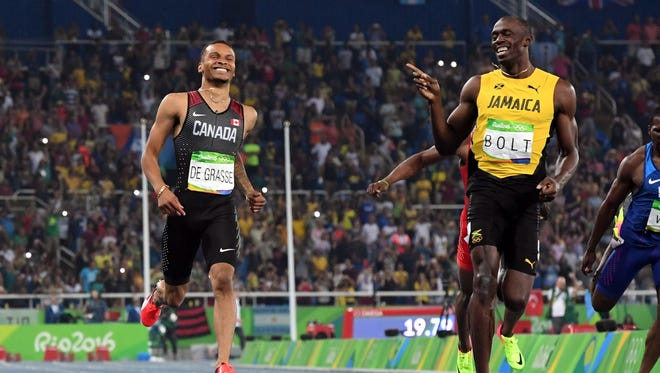 Andre De Grasse (CAN) and Usain Bolt (JAM) react after the men's 200m semifinals in the Rio 2016 Summer Olympic Games at Estadio Olimpico Joao Havelange.