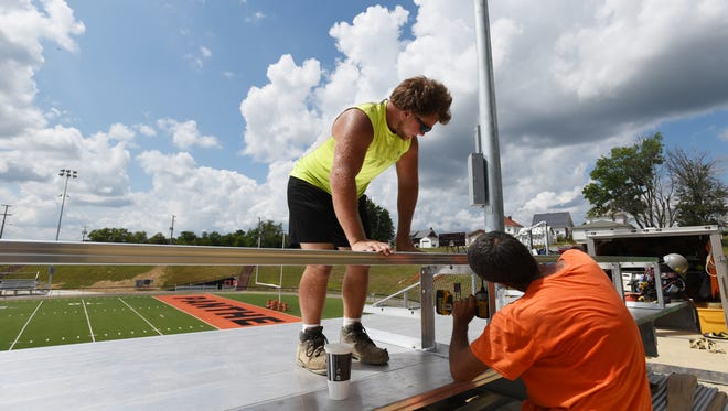 Tanner Flemm, left, and John Clark of JT Seating install new bleachers at New Lexington High School's Jim Rockwell Stadium.