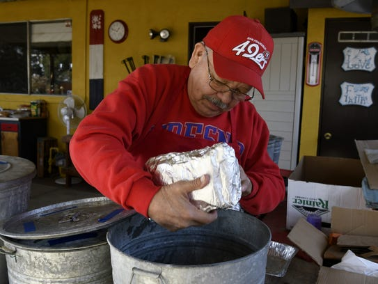 Al Subia adds tamales to a pot to be steamed on Saturday