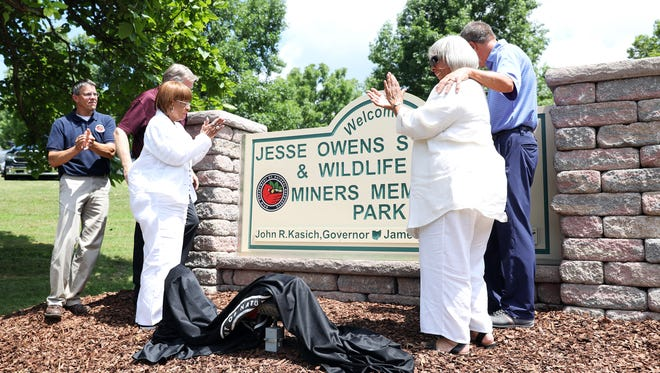 Jesse Owens daughters Beverly Owens Prather, left, and Marlene Owens Rankin, right, applaud after unveiling a sign for Jesse Owens State Park and Wildlife Area during a dedication ceremony on Tuesday.