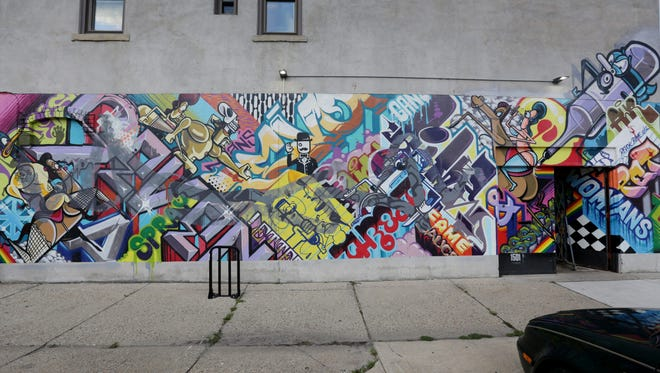 """""""A Man's Threat & a Woman's Pet,"""" a mural by Revok and Rime at 1501 Division in Eastern Market."""