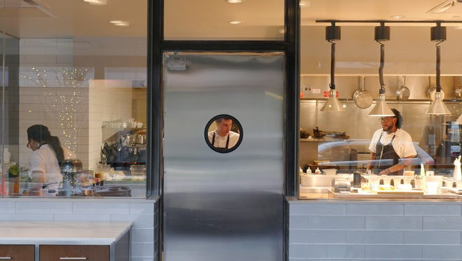 Executive Chef Nick Janutol is framed in the porthole window of the kitchen service door of Forest in Birmingham.