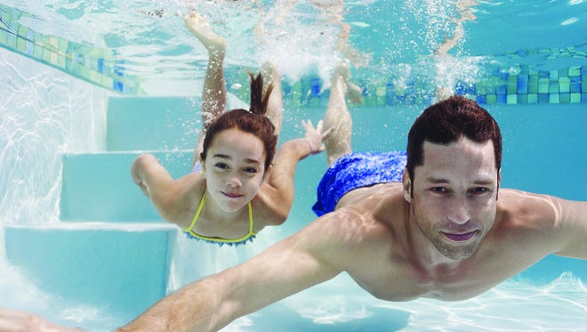 Father and daughter swimming in pool