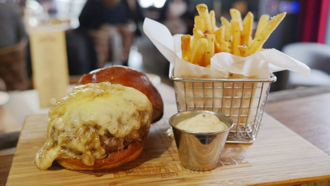 The Townhouse burger features 28-day dry-aged beef with bourbon-caramelized onions and extra-sharp Cabot white cheddar on a brioche bun, served with a side of truffled fries. The Townhouse Detroit restaurant at One Detroit Center in downtown Detroit.