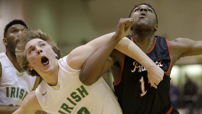 Cathedral Irish Mathew Paligraf (2) fights for position with North Central's Emmanuel Little (14) in the first half of their IHSAA Boys Sectional Tournament game Tuesday, March 1, 2016, evening at Arsenal Technical High School.