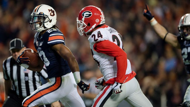 Auburn wide receiver Ryan Davis (23) runs for a touchdown as Georgia strong safety Dominick Sanders (24) attempts to stop him during the NCAA football game between Auburn and Georgia on Saturday, Nov. 11, 2017, in Auburn, Ala.